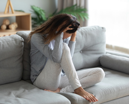 young woman holding head struggling with anxiety