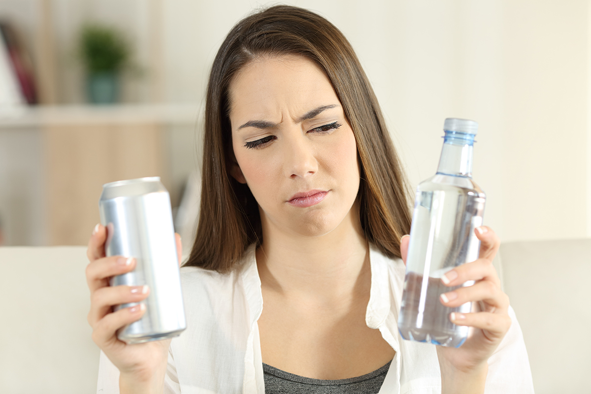 woman deciding between water or a beer wondering, am I an alcoholic